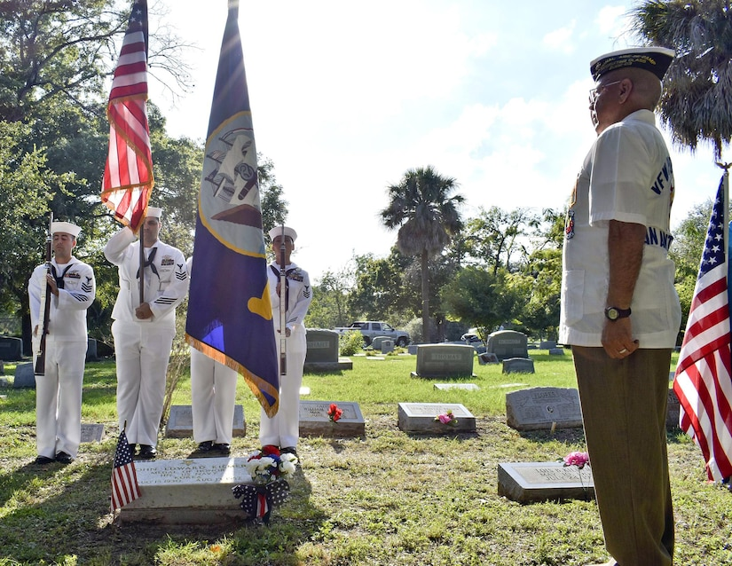A man salutes a color guard standing in front of a gravesite in a cemetery.