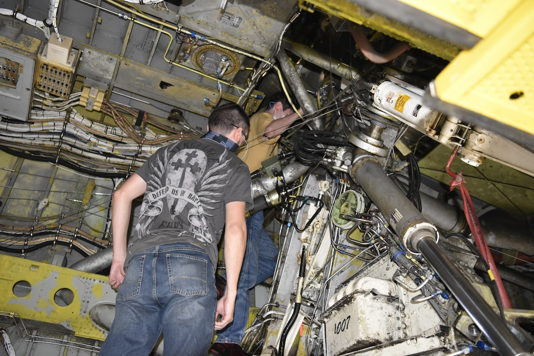 Two men looking at underneath area of aircraft.