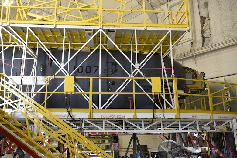 Photo of aircraft in hangar with scaffolding around it.