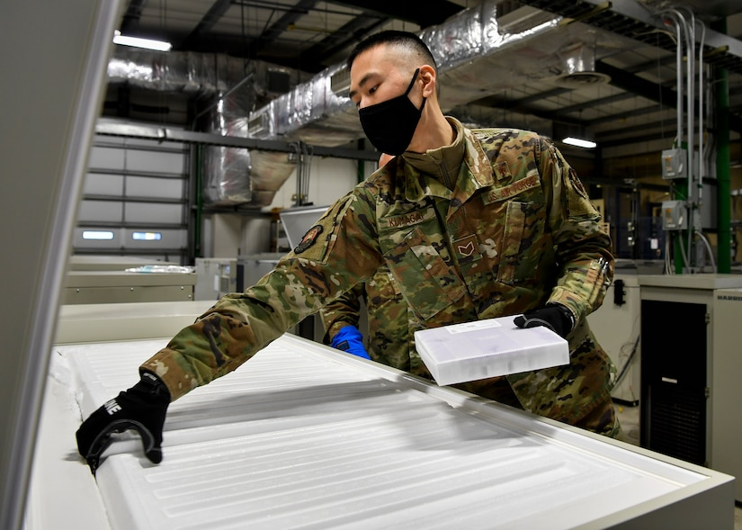 Airman places batch of vaccine in a freezer.