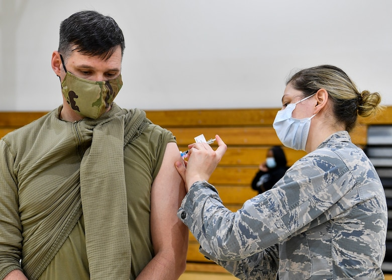 Chief Master Sgt. Spence Johnson, 87th Security Forces Squadron superintendent, receives the COVID-19 vaccine at the Point of Dispensing on Joint Base McGuire-Dix-Lakehurst, New Jersey, Dec. 31, 2020. In accordance with the Department of Defense vaccination plan, the 87th Medical Group prioritized medical care providers, emergency services, safety personnel, and deploying forces to receive the vaccine before other members of the DoD population. (U.S. Air Force photo by Staff Sgt. Jake Carter)