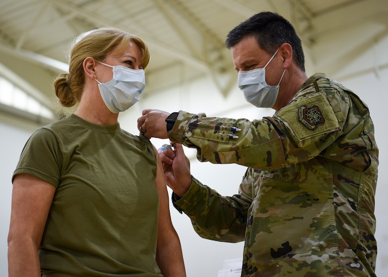 Maj. Dayla Gillispie, 87th Medical Group Family Health Clinic flight commander, receives the first COVID-19 vaccination on Joint Base McGuire-Dix-Lakehurst, New Jersey, from her husband, Lt. Col. Timothy Gillispie, 87th MDG Warrior Clinic flight commander, Dec. 31, 2020. Gillispie said receiving the vaccine was an honor and the next step to eliminating COVID-19. (U.S. Air Force photo by Senior Airman Shay Stuart)