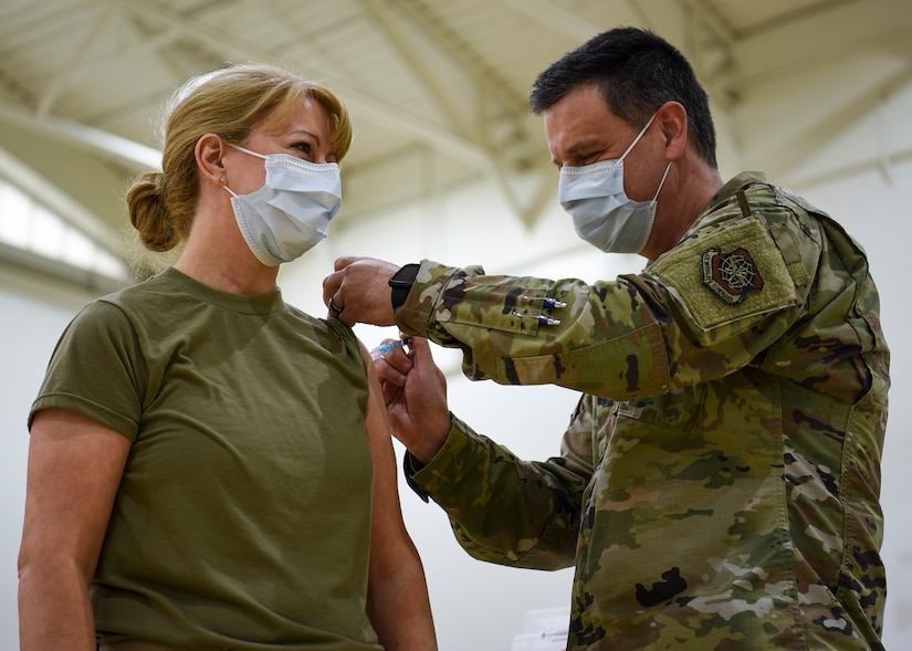 Airman administers shot to another service member.