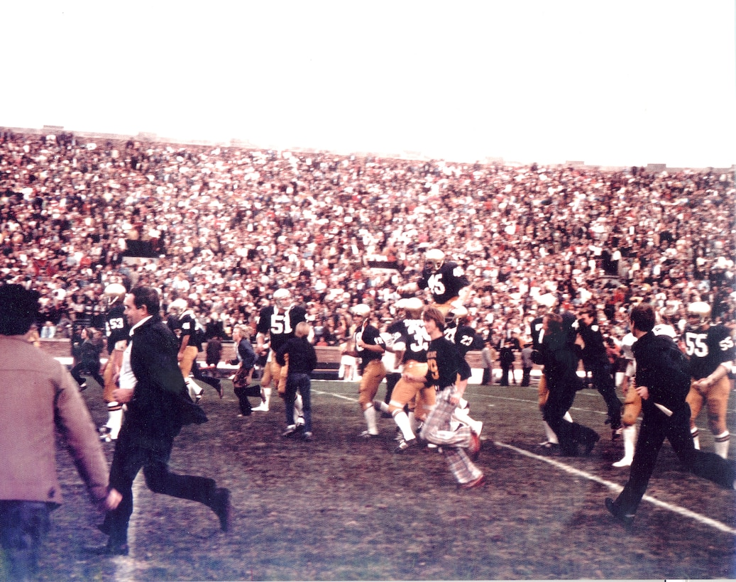 People are running off a football field as a football player is carried by teammates on their shoulders. In the background, the stands are filled with people.