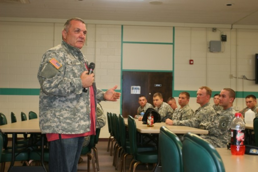 A man speaks into a microphone as soldiers sit at tables to listen.