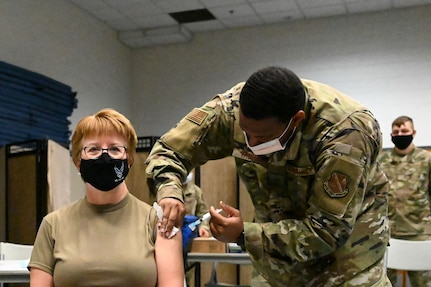 Image of Surgeon General receiving vaccine from an Airman.