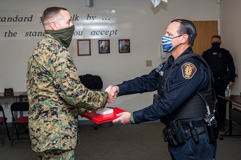 U.S. Marine Corps Lt. Col. Matthew Dowden, left, commanding officer of 2nd Tank Battalion, 2nd Marine Division, presents Michael Walusz, right, a police officer with the Marine Corps Base Camp Lejeune Provost Marshal's Office (PMO), the Lifesaving Award at PMO on MCB Camp Lejeune, North Carolina, Dec. 16, 2020. Walusz received the award for his life-saving actions following an accident in which a Marine with 2nd Tank Battalion was severely injured. (U.S. Marine Corps photo by Lance Cpl. Christian Ayers)