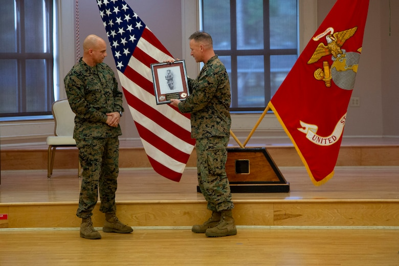 U.S. Marine Corps Col. Todd W. Ferry, right, deputy commander, Marine Corps Installations East- Marine Corps Base Camp Lejeune, presents Sgt. Maj. Charles A. Metzger, left, outgoing sergeant major for MCIEAST-MCB Camp Lejeune, a parting gift from the staff during a relief and appointment ceremony at Marston Pavilion on MCB Camp Lejeune, North Carolina, Dec. 21, 2020. Metzger, relinquished his duties to Sgt. Maj. Robert M. Tellez and retired after 30 years of honorable service to the Marine Corps. (U.S. Marine Corps photo by Cpl. Ginnie Lee)