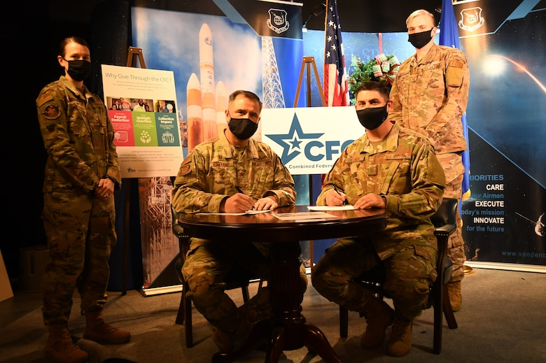 Col. Anthony Mastalir, 30th Space Wing commander, and Chief Master Sgt. Jason DeLucy, 30th SW command chief, sign the proclamation to kick-off the Combined Federal Campaign Dec. 11, 2020, at Vandenberg Air Force Base, Calif.