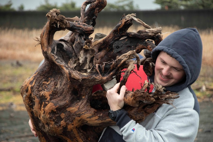 キャンプ富士に所属するモーニー上等兵が12月30日、沼津市の海岸で清掃活動に参加、大きな木の株を除去しています。