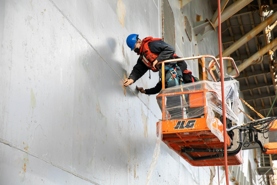 Sailors in an elevated platform clean the side of a ship.