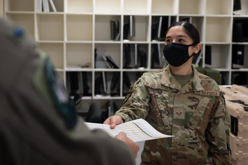 Senior Airman Krystal De Los Santos, 37th Bomb Squadron aviation resource management, hands a document to a U.S. Air Force B-1B Lancer pilot, at Andersen Air Force Base, Guam, in support of a Bomber Task Force mission, Dec. 23, 2020. Several B-1B aircraft deployed to Andersen AFB as part of U.S. Strategic Command's support to the National Defense Strategy objectives of strategic predictability and operational unpredictability by using a mix of different aircraft to and from various dispersed U.S. bases and other departure and arrival points, to include Guam. (U.S. Air Force photo by Senior Airman Tristan Day)