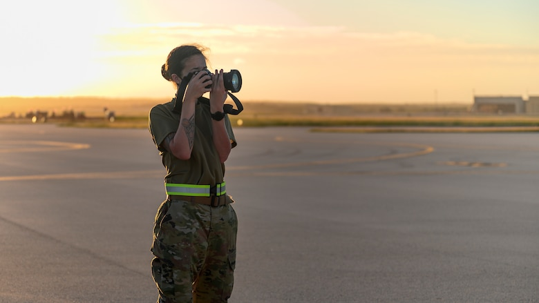 Senior Airman Tristan Day, 341st Missile Wing photojournalist, photographs Bomber Task Force mission operations, at Andersen Air Force Base, Guam, Dec. 15, 2020. As a photojournalist, Day captures the U.S. Air Force mission in the form of written words, photos and videos. (U.S. Air Force photo by Airman 1st Class Austin McIntosh)