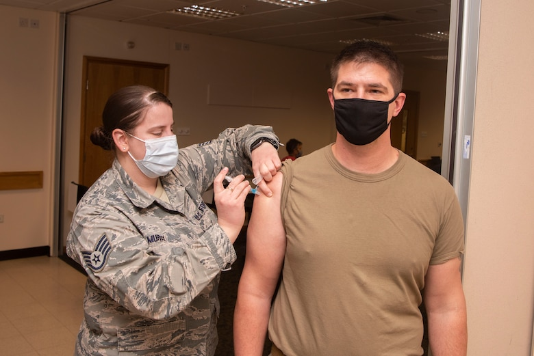 U.S. Air Force Staff Sgt. Anna Murray, 48th Healthcare Operations Squadron immunizations technician, administers a dose of the COVID-19 vaccine to a Team Mildenhall Airman Jan. 5, 2021, at Royal Air Force Lakenheath, England. Medical personnel, individuals maintaining national security and installation functions, deploying forces and those at high risk will be the first to receive the vaccine. (U.S. Air Force photo by Senior Airman Joseph Barron)
