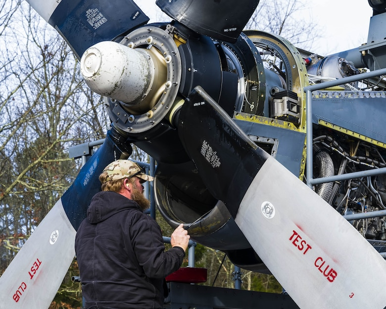 Todd Jobst, Contract Field Team member, inspects the air intake of a newly upgraded T-56 Rolls Royce 3.5 modified engine on Jan. 4, 2021, at Little Rock Air Force Base, Ark. An operational check out of all engine and propeller systems are performed, to ensure the systems meet performance specifications before delivery to an Air Force Reserve or Air National Guard C-130H Hercules squadron. Contracted mechanics at the engine test cell facility ensure each engine is serviceable, troubleshoots any issues, and performs additional inspections. (U.S. Air Force Reserve photo by Maj. Ashley Walker)