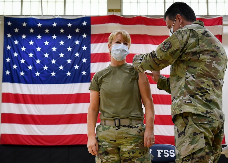 Maj. Dayla Gillispie, 87th Medical Group Family Health Clinic flight commander, receives the first COVID-19 vaccination on Joint Base McGuire-Dix-Lakehurst, New Jersey, from her husband, Lt. Col. Timothy Gillispie, 87th MDG Warrior Clinic flight commander, Dec. 31, 2020. Gillispie said receiving the vaccine was an honor and the next step to eliminating COVID-19. (U.S. Air Force photo by Staff Sgt. Jake Carter)
