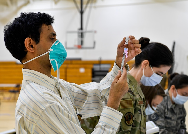 87th Medical Group personnel prepare syringes containing the COVID-19 vaccine at the Point of Dispensing on Joint Base McGuire-Dix-Lakehurst, New Jersey, Dec. 31, 2020. After receiving the initial vaccination, members will require a second dose to be considered vaccinated. (U.S. Air Force photo by Staff Sgt. Jake Carter)