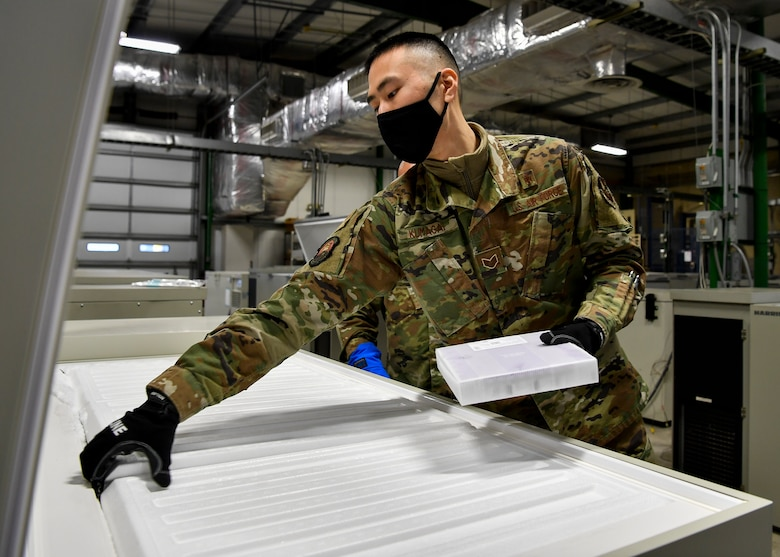 U.S. Air Force Staff Sgt. Akira Kumagai, Armed Services Whole Blood Processing Laboratory – East member, places a batch of COVID-19 vaccines inside a freezer on Joint Base McGuire-Dix-Lakehurst, New Jersey, Dec. 31, 2020. The vaccines, which must be temperature controlled, were placed into freezers before being sent to the McGuire Fitness Center for distribution. (U.S. Air Force photo by Staff Sgt. Jake Carter)