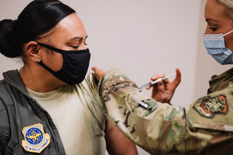 Master Sgt. Renee Cheatham, 375th Aeromedical Evacuation Squadron aeromedical evacuation technician, receives one the first COVID-19 inoculations on Scott Air Force Base, Ill., Jan 6, 2021. The COVID-19 vaccines will be available on a voluntary basis in which early vaccination participation is highly encouraged for priority personnel; masks and physical distancing will still be necessary until a large proportion of the population is vaccinated and the vaccine is proven to provide long-term protection. (U.S. Air Force photo by Tech. Sgt. Jordan Castelan)