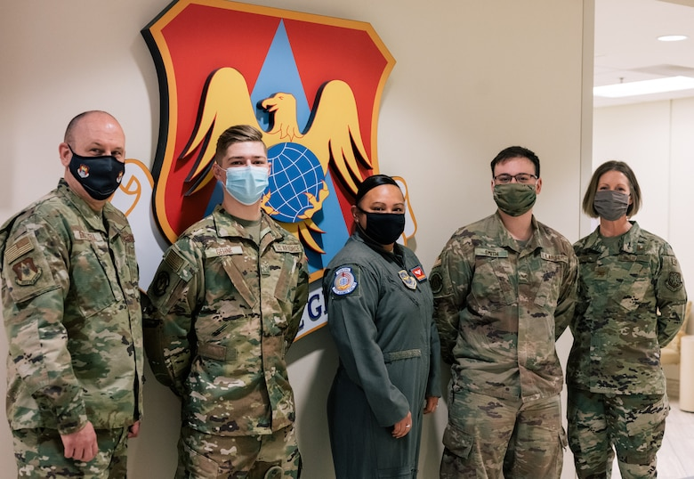 Airman 1st Class James Gehne, 375th Civil Engineer Squadron firefighter, second from the left, Master Sgt. Renee Cheatham, 375th Aeromedical Evacuation Squadron aeromedical evacuation technician, middle, and Senior Airman Matthew Smith, 375th Security Forces patrolman, second from the right, are congratulated by Chief Master Sgt. Chuck Frizzell, 375th Air Mobility Wing command chief, left, and Col. Angela Ochoa, 375th AMW vice-commander, right, for being the first three members of Team Scott to receive a COVID-19 inoculation on Scott Air Force Base, Ill., Jan 6, 2021. The Department of Defense prioritizes personnel to receive the vaccines based on Center of Disease Control guidance and the DoD COVID Task Force's assessment of unique DoD mission requirements. The DoD Prioritization Schema prioritizes those providing direct medical care, maintaining essential national security and installation functions, deploying forces and beneficiaries at the highest risk for developing serious illness before other members of the DoD population. (U.S. Air Force photo by Tech. Sgt. Jordan Castelan)