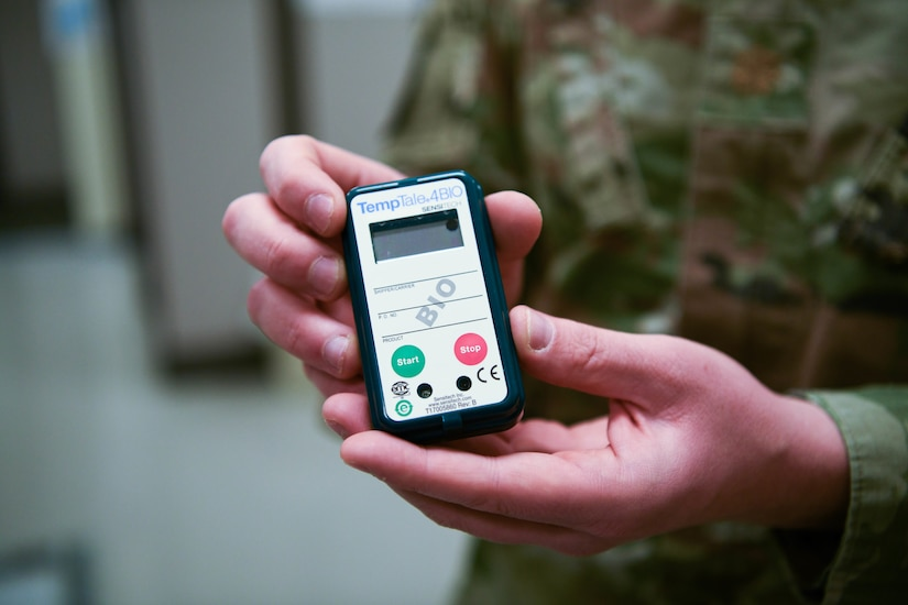 A soldier holds a temperature check device.