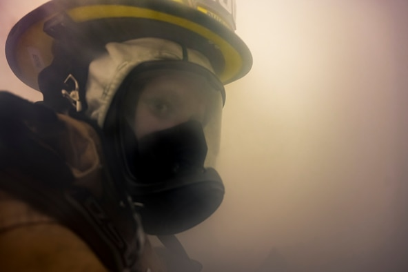 Alexis Pihoker, Pittsburgh Airport Authority firefighter, walks through a smoke-filled room searching for people in need of rescue during a munitions storage area fire drill at the Pittsburgh International Airport Air Reserve Station, Pennsylvania, Dec. 10, 2020.