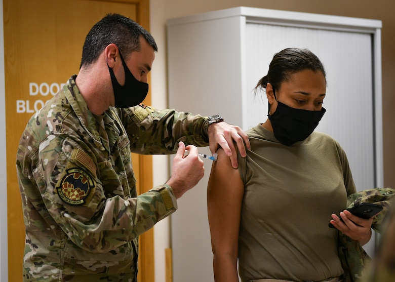 A medical technician assigned to the 48th Medical Group gives the COVID-19 vaccine to an Airman at Royal Air Force Lakenheath, England, Jan. 6, 2021. Each phase of the vaccine distribution process is designed to safely inoculate Department of Defense personnel from COVID-19 as quickly as possible. (U.S. Air Force photo by Senior Airman Madeline Herzog)