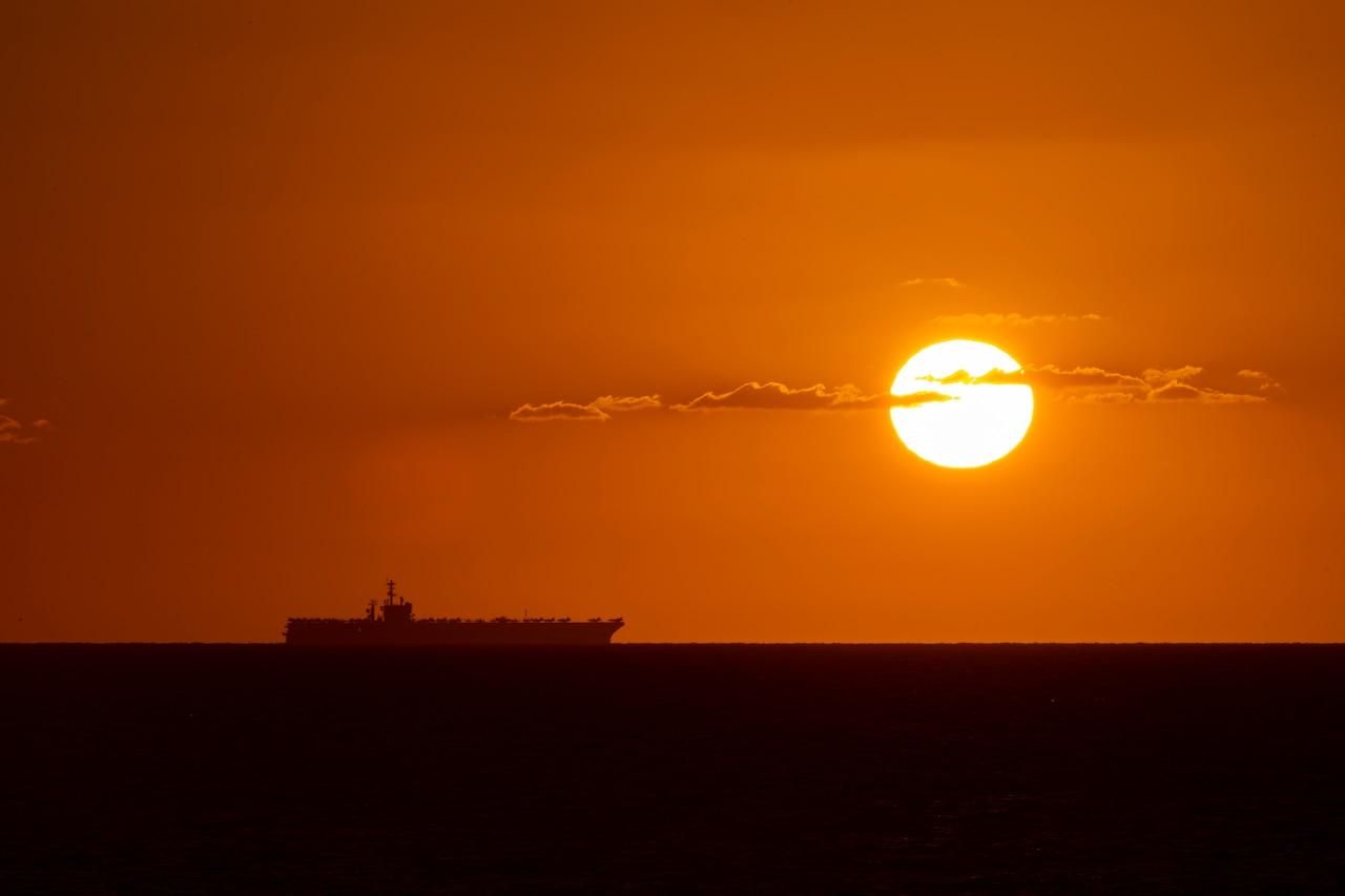 A ship sails on the ocean amid an orange horizon.