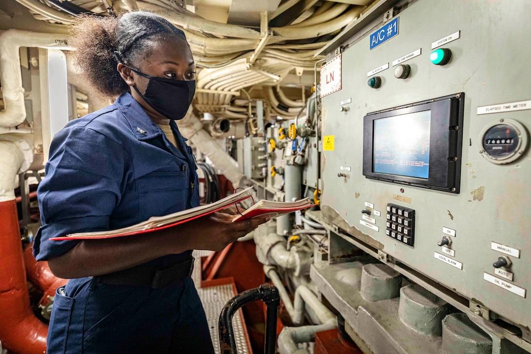 A sailor wearing a mask watches a machine.