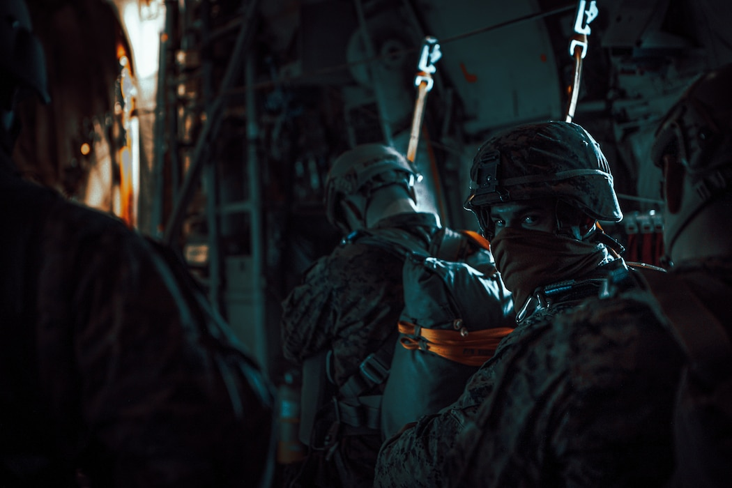 U.S. Marines with 1st Radio Battalion, I Marine Expeditionary Force Information Group, begin safety checks during a static-line jump exercise Dec. 10, 2020, from a KC-130J Super Hercules. The exercise allowed Marines of 1st Radio Battalion to practice an airborne deployment with cargo drops and static-line jumpers at Marine Corps Base Camp Pendleton, California. (U.S. Marine Corps photo by Lance Cpl. Isaac Velasco)