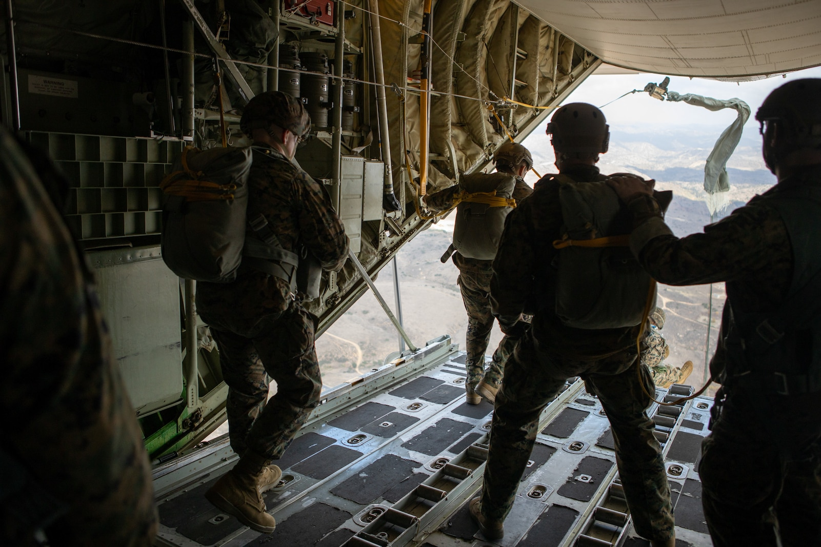 U.S. Marines with 1st Radio Battalion, I Marine Expeditionary Force Information Group, prepare to exit a KC-130J Super Hercules aircraft during a static-line parachute jump Dec. 10, 2020. The training allowed Marines of 1st Radio Battalion to practice an airborne deployment with cargo drops and static-line jumpers at Marine Corps Base Camp Pendleton, California. (U.S. Marine Corps photo by Lance Cpl. Isaac Velasco)