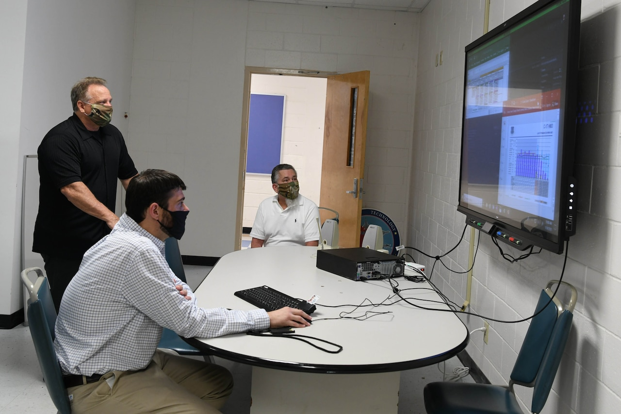 Three men -- two seated and one standing -- gather around a table and look at a giant computer screen hanging on a wall. A computer and keyboard sit on the table.