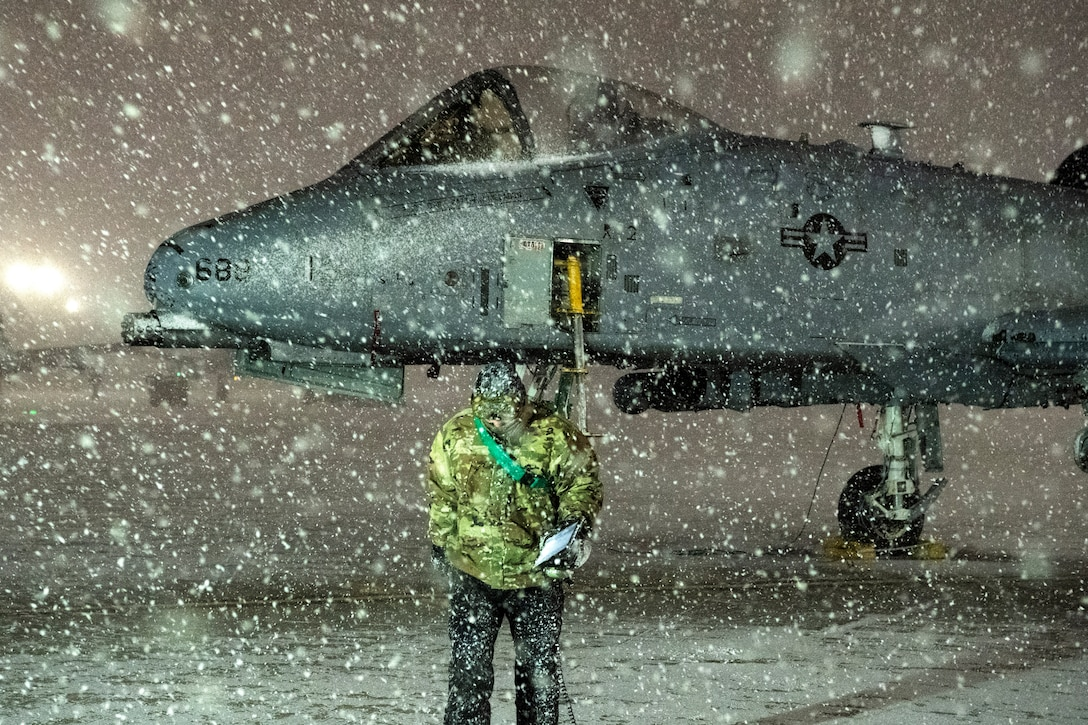 An airman finishes servicing an A-10 while in the snow.