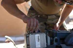 U.S. Air Force Senior Airman Ryan Davis, 724th Expeditionary Air Base Squadron air terminal operations center journeyman, replaces a cap after putting oil into a Halvorsen 25K-Loader, at Nigerien AB 201, Agadez, Niger, Jan 4, 2021. ATOC's mission is that each plane is handled quickly and safely. (U.S. Air Force photo by Senior Airman Gabrielle Winn