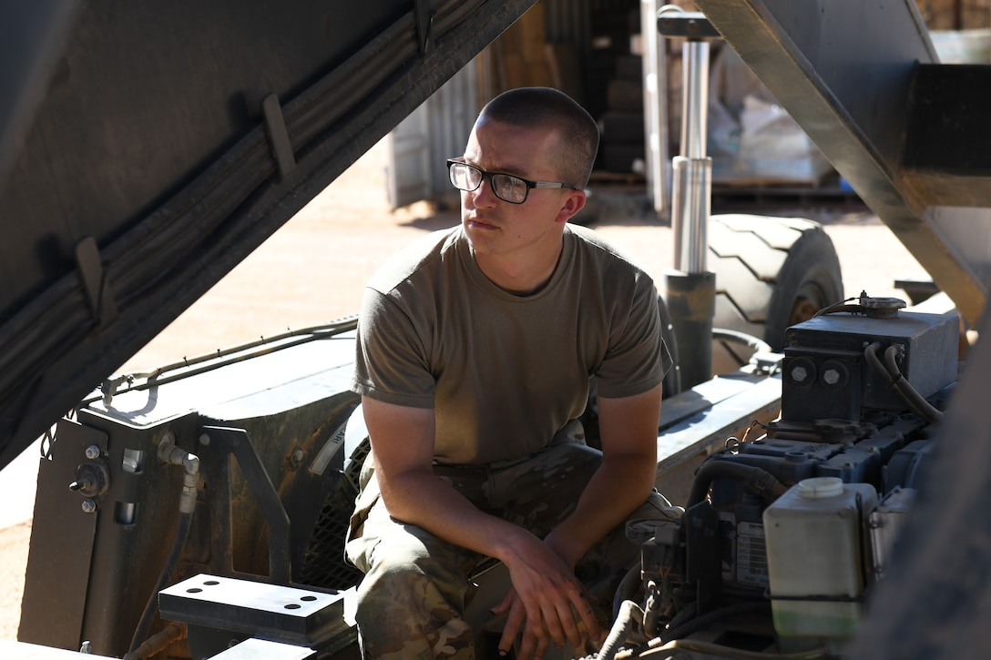 U.S. Air Force Senior Airman Ryan Davis, 724th Expeditionary Air Base Squadron air terminal operations center journeyman, cools off from the desert heat while servicing a Halvorsen 25K-Loader, at Nigerien Air Base 201, Agadez, Niger, Jan 4, 2021. ATOC's main purpose at AB 201 is to move cargo, mail and passengers in and out of the installation ensuring cargo gets into the hands of the users and passengers get to where they need to go. (U.S. Air Force photo by Senior Airman Gabrielle Winn)