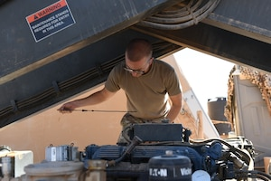 U.S. Air Force Senior Airman Ryan Davis, 724th Expeditionary Air Base Squadron air terminal operations center journeyman, checks the oil level in a Halvorsen 25K-Loader, at Nigerien Air Base 201, Agadez, Niger, Jan 4, 2021. ATOC is responsible for air transportation operations including cargo upload/download, cargo processing, special handling, passengers, and load planning. (U.S. Air Force photo by Senior Airman Gabrielle Winn)