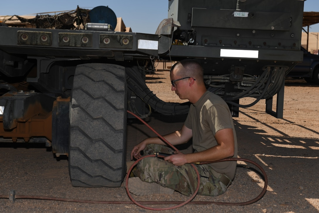 U.S. Air Force Senior Airman Ryan Davis, 724th Expeditionary Air Base Squadron air terminal operations center journeyman, puts air in a Halvorsen 25K-Loader tire, at Nigerien Air Base 201, Agadez, Niger, Jan 4, 2021. These machines are used to upload and download pallets, pallet trains, and rolling stock on cargo aircraft. (U.S. Air Force photo by Senior Airman Gabrielle Winn)