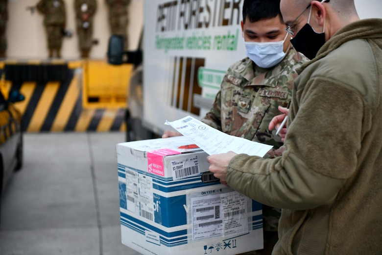 U.S. Air Force Staff Sgt. Bernardino Sunglao, 31st Medical Support Squadron war reserve materiel non-commissioned officer in charge, left, carries a box of Moderna COVID-19 vaccines at Aviano Air Base, Italy, Jan. 7, 2021. Personnel from across the 31st Medical Group attended the vaccine's highly anticipated arrival. (U.S. Air Force photo by Staff Sgt. K. Tucker Owen)