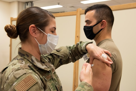 Female medic administering a vaccine to a male Airman