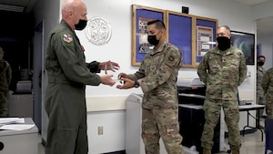 Commander handing award to Airman.