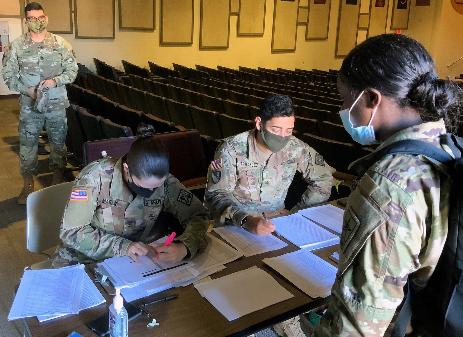 Pfc. Shavarianna Burton is greeted at the first station for Holiday Block Leave reintegration screening as Lt. Col. Nadia M Pearson, MEDCoE command surgeon and Command Sgt. Major Gilberto Colon, 32nd Medical Brigade Command Sergeant Major, look on.