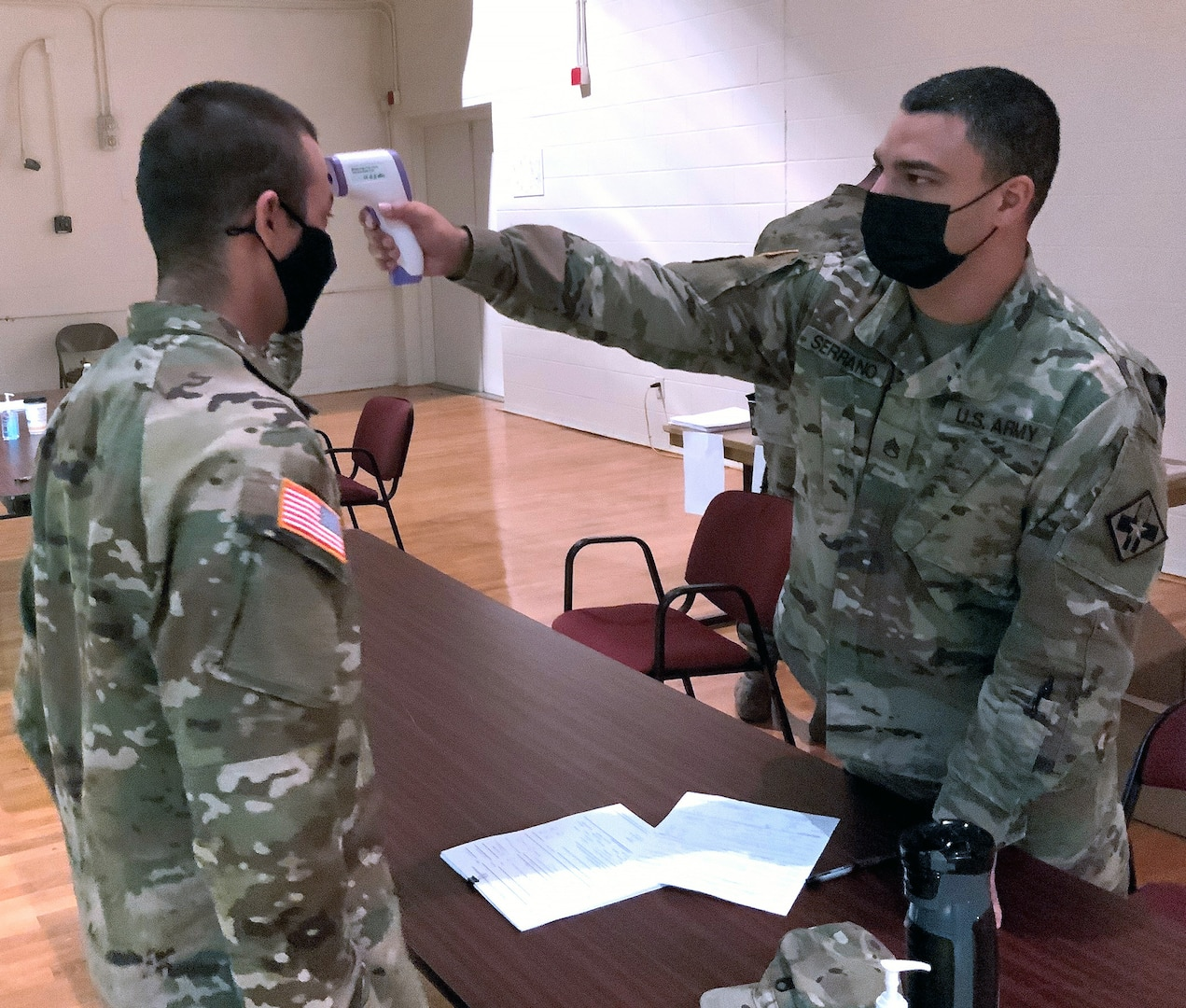 Staff Sgt. Eric Serrano, an Instructor with the 32nd Medical Brigade, screens a returning Holiday Block Leave Soldier.