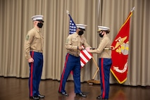 U.S. Marine Sgt. Maj. Chester Wilson III, center, outgoing district sergeant major, passes a sword to Col. Heather J. Cotoia, right, commanding officer 4th Marine Corps District, during a relief and appointment ceremony at the Defense Logistics Agency, New Cumberland, Pennsylvania, Dec. 22, 2020. Sgt. Maj. Kenneth L. Kuss took over the 4th Marine Corps District senior enlisted advisor position from Wilson. (U.S. Marine Corps photo by Gunnery Sgt. Valerie Nash)