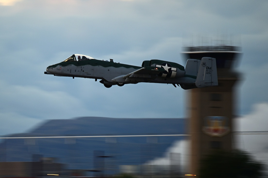 Photo of an A-10 Thunderbolt II flying across the Davis-Monthan Air Force Base air traffic control tower