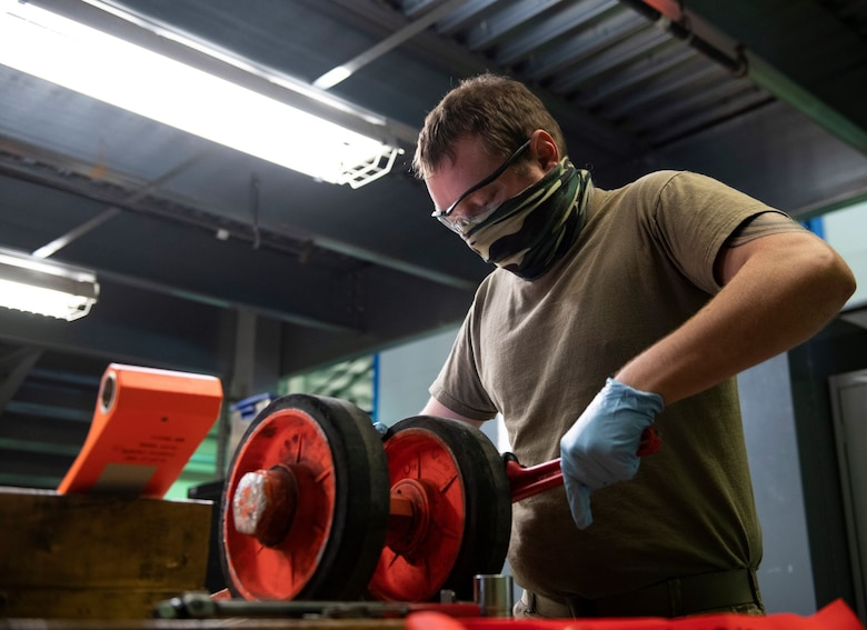 Senior Airman Adam Sherman, 9th Aircraft Maintenance Squadron (AMXS) support technician, removes the wheels of a U-2 Dragon Lady pogo-wheel assembly on Beale Air Force Base.