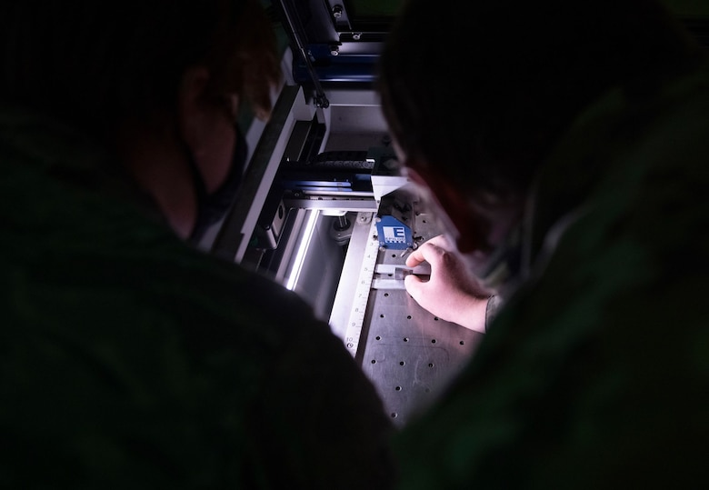 Airman 1st Class Hannah Kinter, left, and Senior Airman Adam Sherman, 9th Aircraft Maintenance Squadron (AMXS) support technicians prepare to laser engrave a tool on Beale Air Force Base.