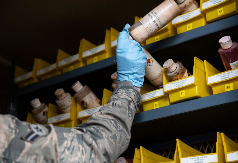 Airman 1st Class Hannah Kinter, 9th Aircraft Maintenance Squadron (AMXS) support technician, places hazardous material into storage on Beale Air Force Base.