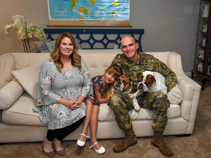 A man, woman and child sitting on a couch with two dogs