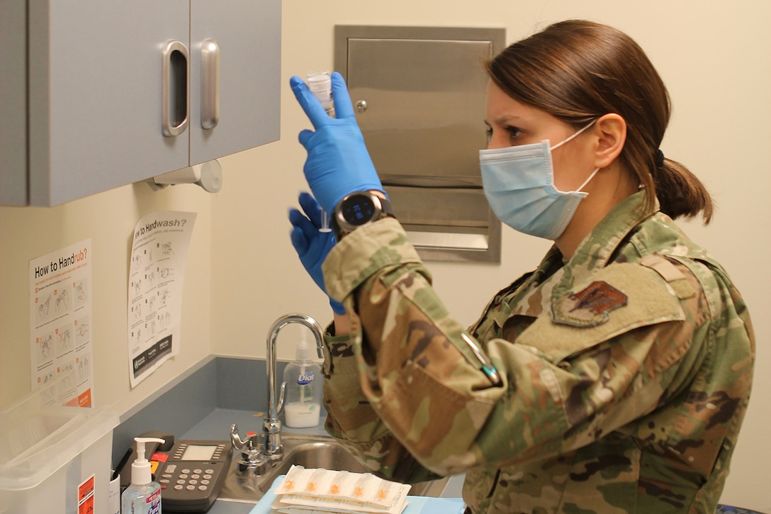 Tech. Sgt. Kirstin James, a medic with the 127th Medical Group, prepares to administer one of the first COVID-19 vaccinations at Selfridge Air National Guard Base, Mich., Jan. 8, 2021. The 127th MDG began administering the vaccination at Selfridge ANGB to the base's first responders and other mission-essential personnel. More widespread distribution of the vaccine to base personnel is scheduled throughout the month.