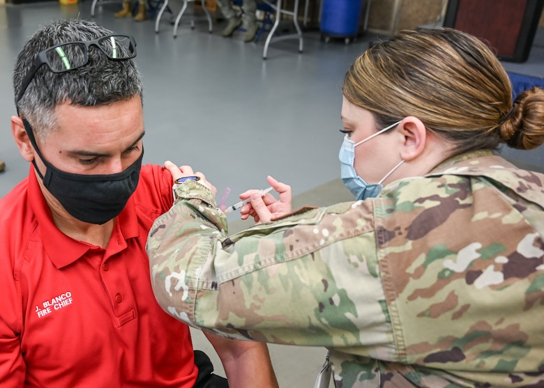 Javie Blanco, 775th Civil Engineer Squadron fire chief, receives his COVID-19 vaccination.
